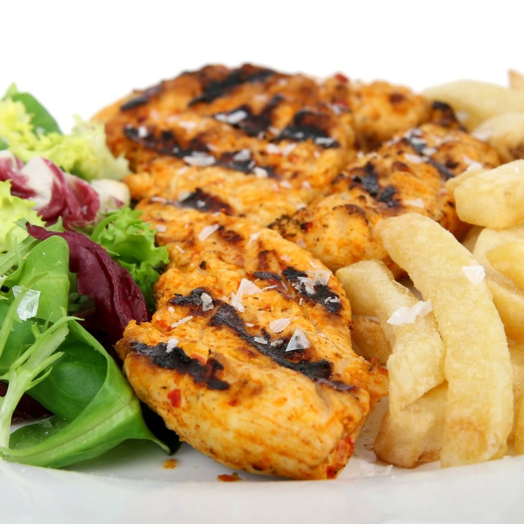 Summer barbeque chicken with salad and French fries, macro close up isolated on white
